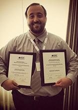 Justin Toth holding awards from the ASAC conference.