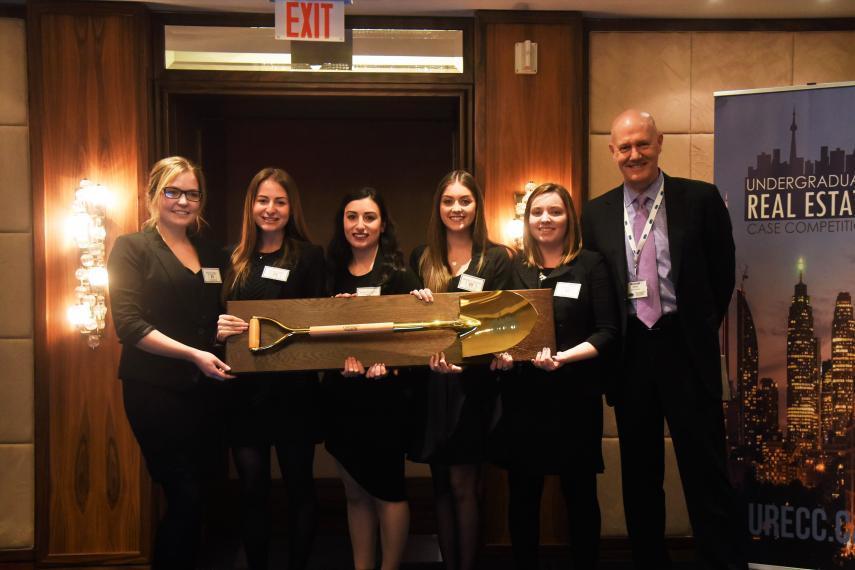 Winning team holds golden shovel award with Michael Emory