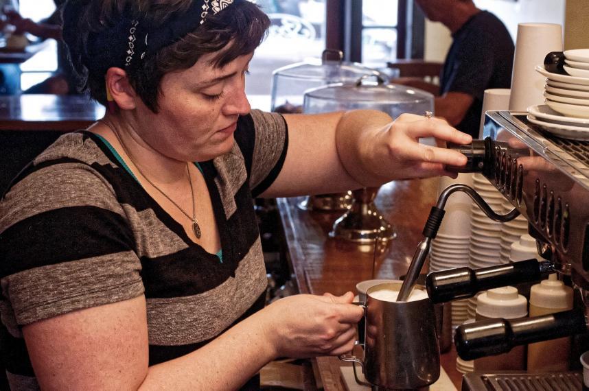 barista foaming coffee in cup