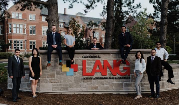 Students standing beside the Lang School logo