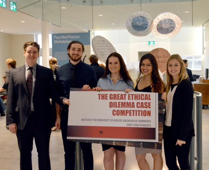 First-year students pose with the Great Ethical Dilemma Case Competition sign