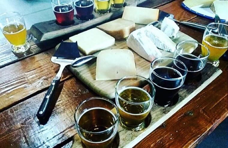 Photo of cheese platter and flight of beer