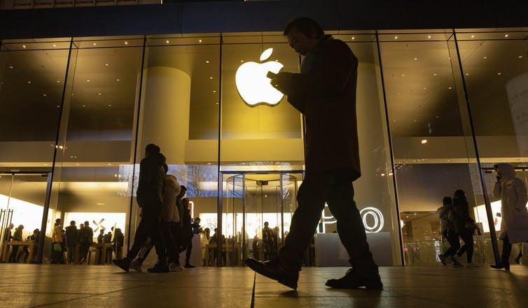 people walking past Apple store