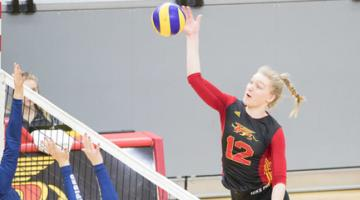 female student athlete playing volleyball