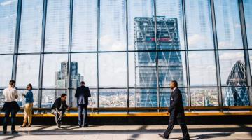 photo of people walking through corporate setting with skyscrapers and city in background