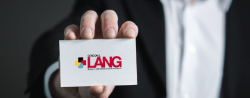 hand holding a lang school business card