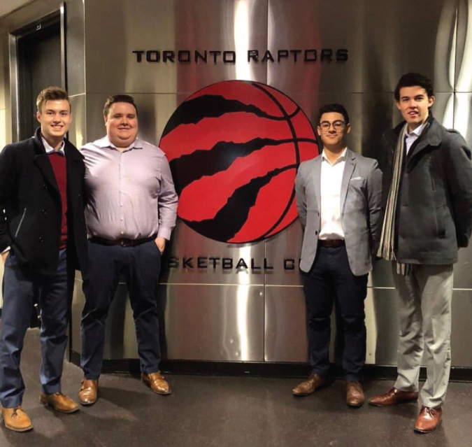 students infront of the Toronto Raptors logo