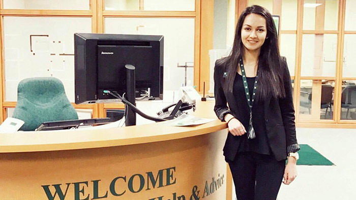 Albina stands by her desk at TD