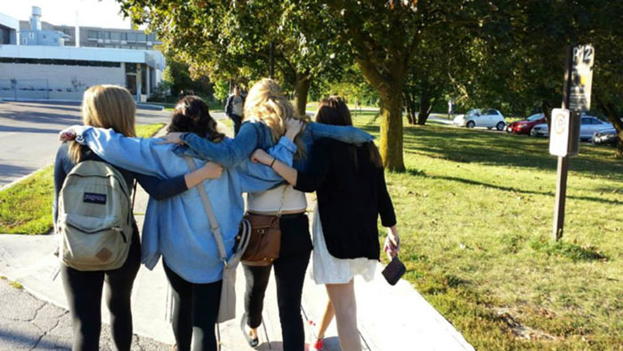 friends walk on campus with their arms around each other
