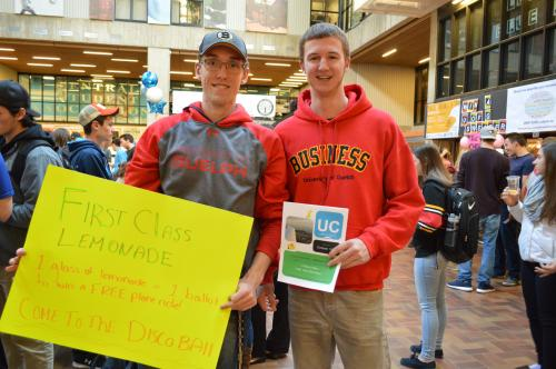 Photo of two male students holding signs for lemonade day in the University Centre