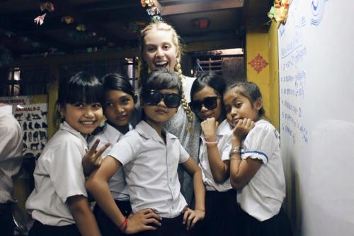 Leah posing with a group of five of her students in cambodia