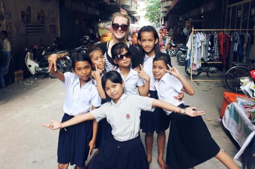 Photo of Leah posing with a group of six students in Cambodia