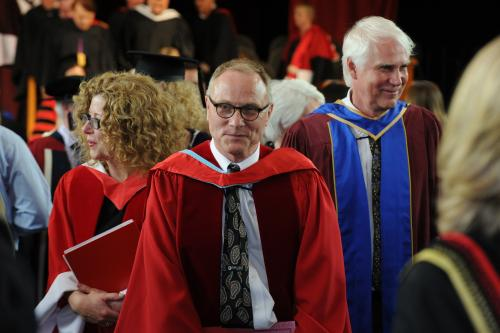 Photo of David Card leaving the convocation ceremony in Memorial Hall
