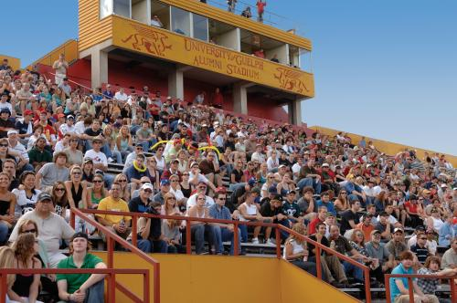 People sitting in alumni stadium watching the homecoming football game