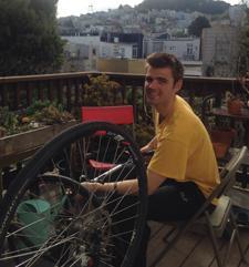 Cole Crawford on balcony working on his bike