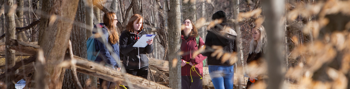 Students stand in snowy wooded area looking at trees