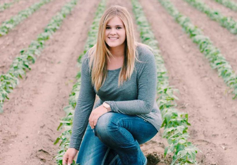Amy kneels in a farmer's field.