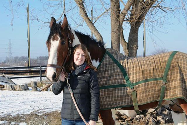 Caleigh outside in winter with horse wearing a blanket.