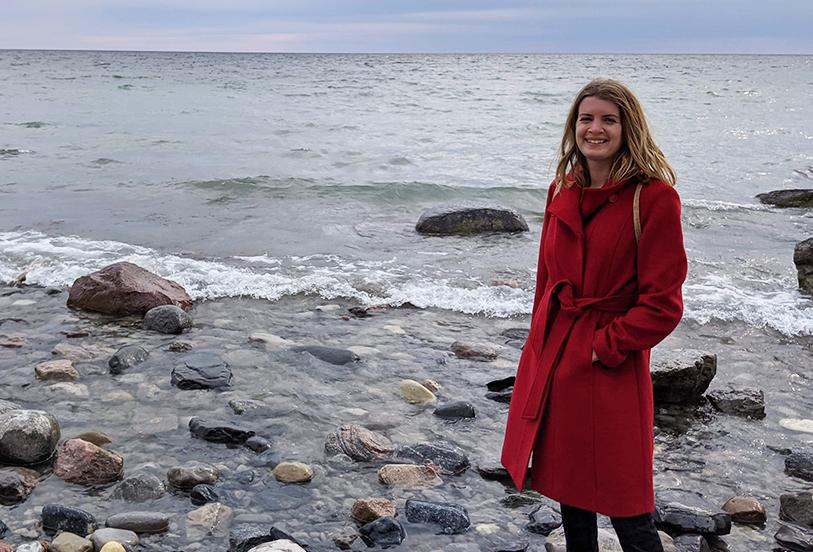 Danielle standing on a shore with a body of water in the background