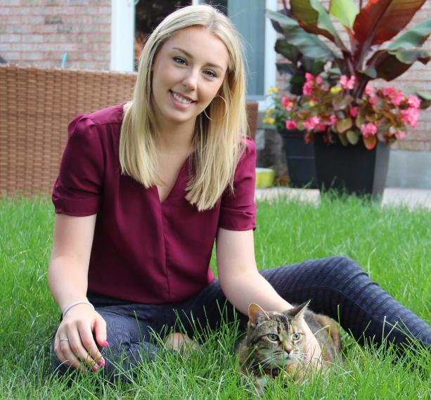 Natalie sits in a yard with a cat.