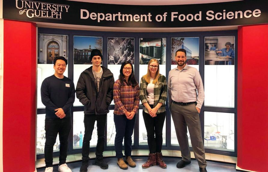 Team of students stands together with a large Department of Food Science banner behind them.