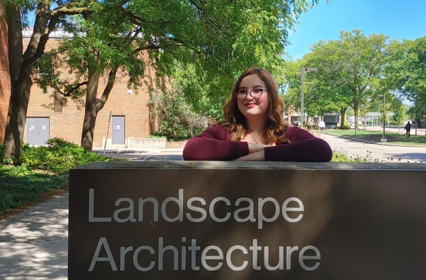 Tatijana standing in front of a sign that says landscape architecture.