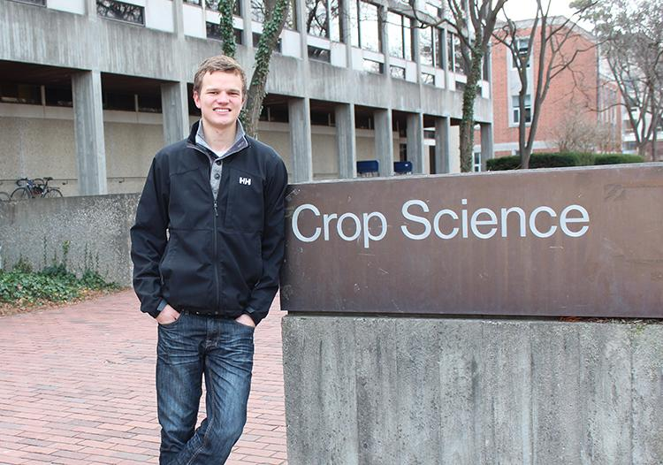"Chris stands outside in jacket beside a sign saying ""Crop Science"""