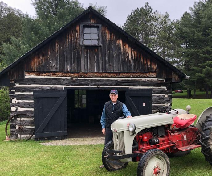 Dave Little standing behnd a red tractor and in front of a log shed