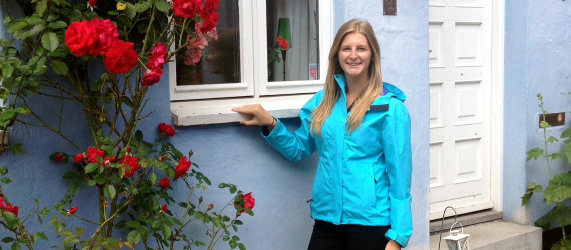 Emma Drake stands at window beside a rose bush.
