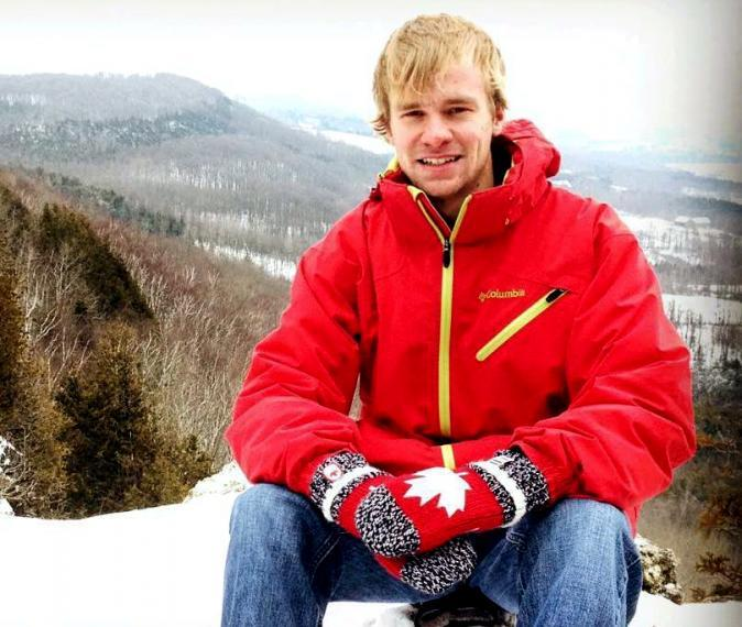 Jeremy sits at the top of a mountain wearing a red coat and mittens.