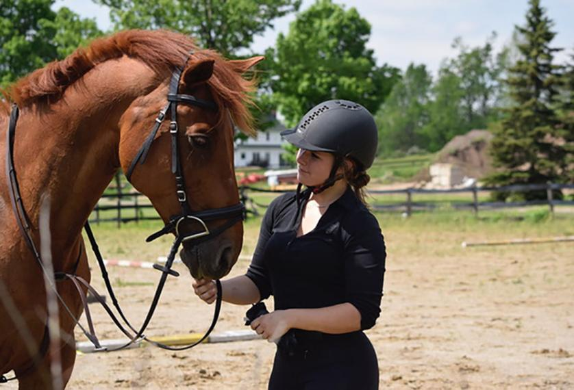 Julia stands beside and looks at brown horse