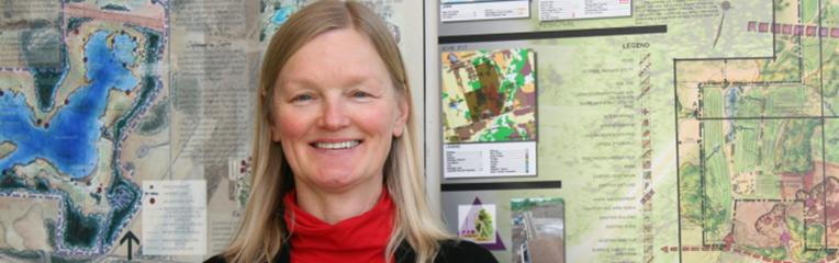 Karen Landman smiling in front of large landscape sketch