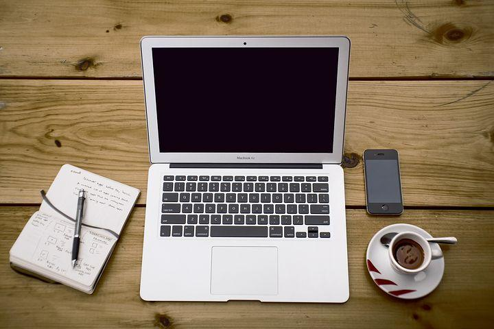 A work station with a laptop, cellphone and notepad