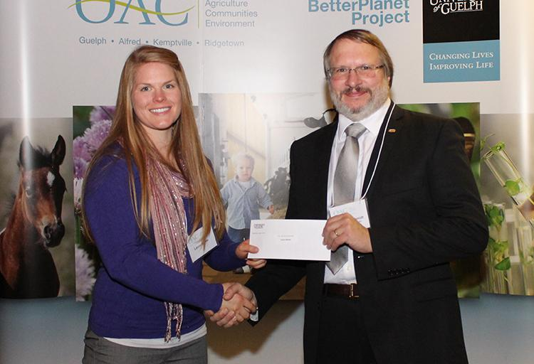 Laura Nanne is presented a cheque by a prof in a suit