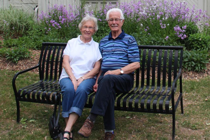 Barb and Joe Maxwell sit on black iron bench in front of garden of purple wild flowers