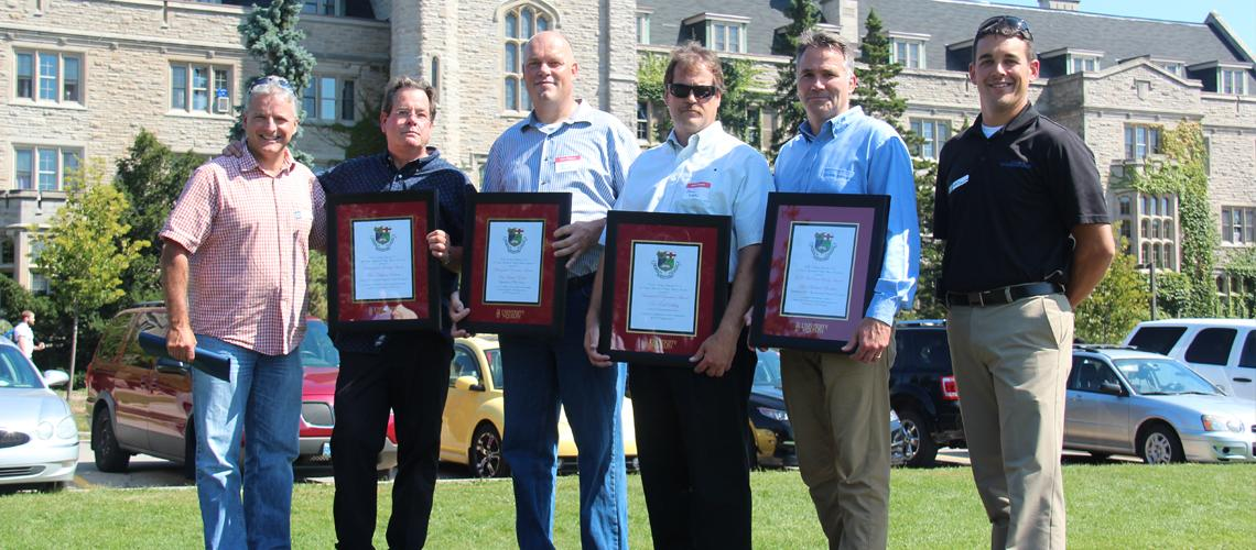 Six men stand in front of Johnston Hall outside, four award winners hold framed certificates