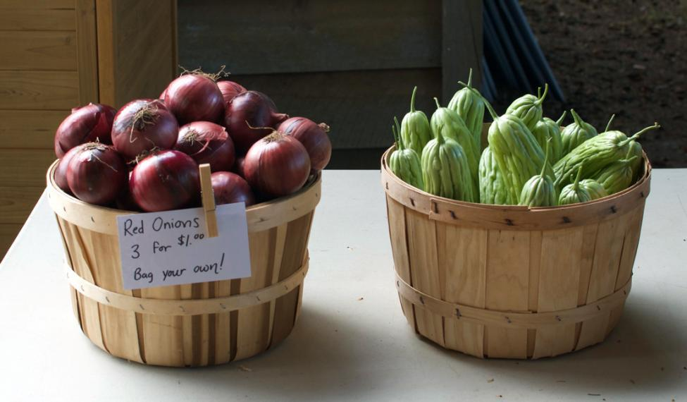 Red onions and green vegetables in baskets