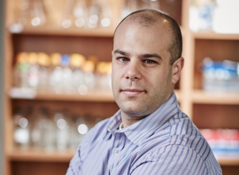 Paul Spagnuolo in front of a wall of pharmaceutical jars
