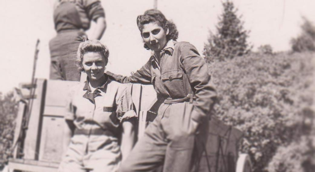 Rosalind and Erika stand together on a cart in work coveralls in 1942