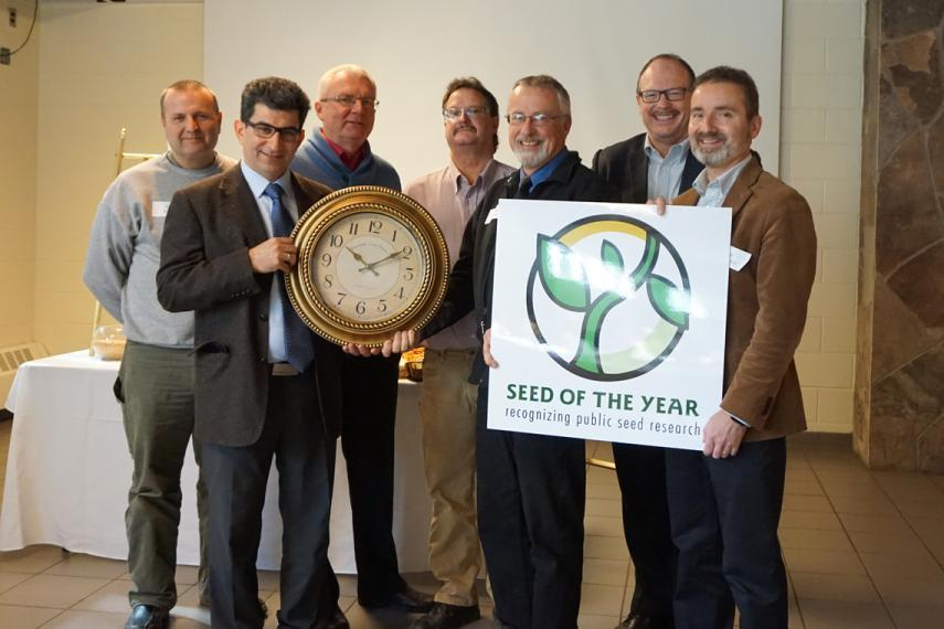 Seven men stand together with large award clock and sign that says Seed of the Year