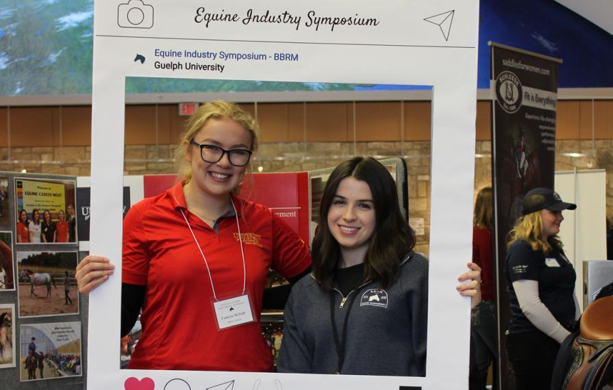 Two female students smile and pose with an Instagram frame