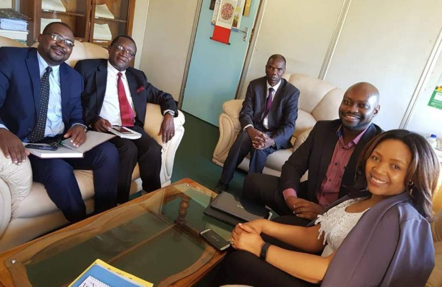 Group of sitting government officials smiling, Tendai sitting with them on the right.