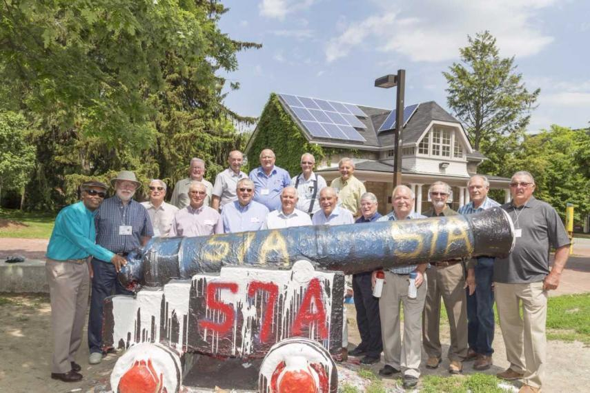 The OAC class of 57 stands around the cannon