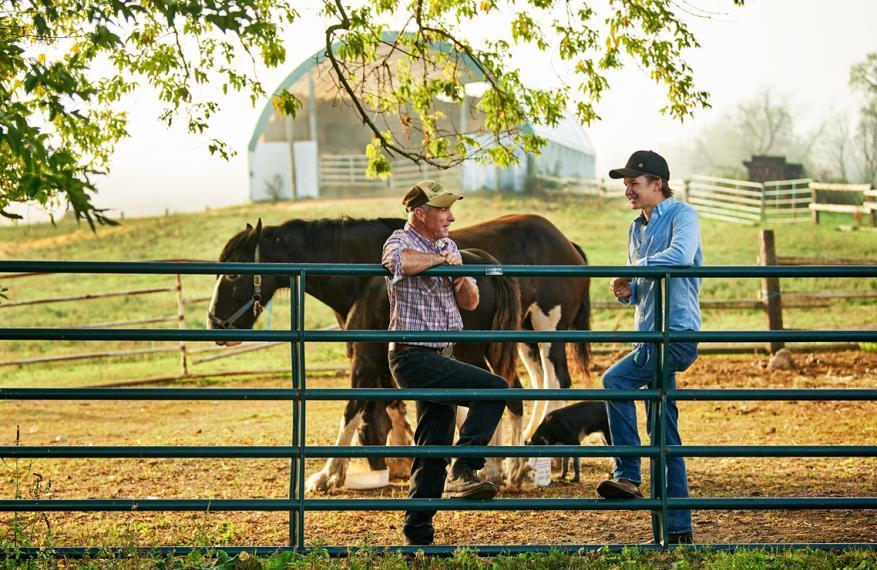 Wyatt McWilliams snd Josh Moran lean on a farm fence post
