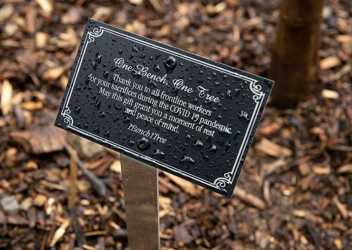 Black plaque with silver text that reads One Bench One Tree. Thank you to all frontline workers for your sacrifices during the COVID 19 pandemic. May this gift grant you a moment of rest and peace of mind. 1Bench1Tree.
