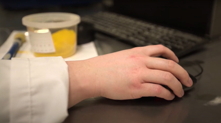 Hand on mouse near key board, with yellow sample container in background