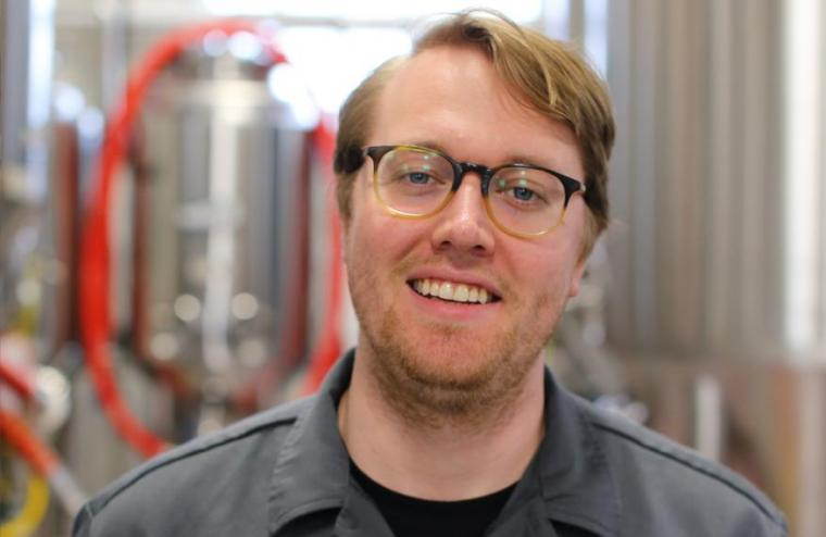 Patrick with brewing equipment behind him