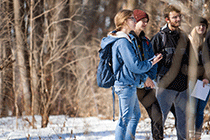 Students standing in a wooded area holding clip boards.