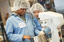 Two students in lab coats and hair nets working with a mixer in a lab.