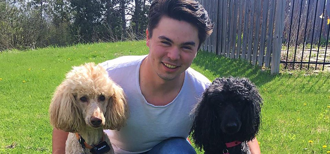 Thomas poses and smiles with two dogs.